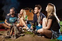 De vrienden die dichtbij vuur, het glimlachen, het spreken, het rusten, het drinken zitten dragen camping royalty-vrije stock afbeeldingen