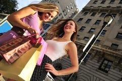 De vrienden die van het meisje in de stad winkelen Stock Foto