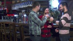 De vrienden drinken bier bij de bar stock foto's