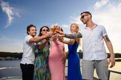 De vrienden drinken champagne op jacht stock fotografie