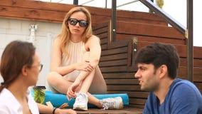 De vrienden drinken koffie en praatje in een informele openluchtkoffie Snel voedsel stock videobeelden