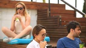 De vrienden drinken koffie en praatje in een informele openluchtkoffie Snel voedsel stock video