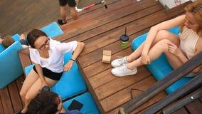 De vrienden drinken koffie en praatje in een informele openluchtkoffie Snel voedsel stock footage