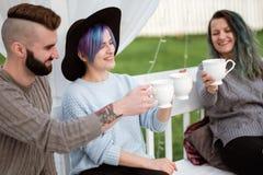 De vrienden drinken thee en hebben een goede tijd op het terras van een buitenhuis royalty-vrije stock fotografie