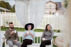 De vrienden drinken thee en hebben een goede tijd op het terras van een buitenhuis stock afbeelding