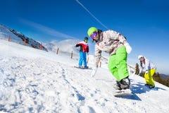 De vrienden en één mens snowboarding bergaf stock fotografie