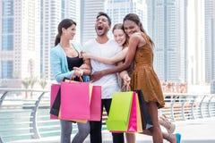 De vrienden gaan winkelend De mooie meisjes in kleding koesteren de kerel whil Stock Foto's
