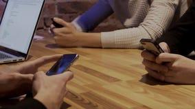 De vrienden gebruiken moderne gadgets bij lijst in in plaats stock videobeelden