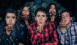 De vrienden groeperen blazende confettien aan de camera in een partij stock afbeeldingen