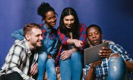 De vrienden hebben pret speelspel op tablet, vrije tijd stock afbeeldingen