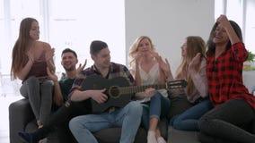 De vrienden het lopen en sprong op de bank en de dans aan gitaar, jongens en meisjes hebben pret bij de huispartij stock video