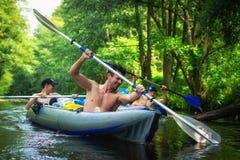 De vrienden in kano met roeispanen zwemmen op bosrivier stock foto's