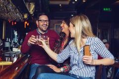 De vrienden kwamen na het werk in een bar voor een paar dranken bijeen - Beeld royalty-vrije stock afbeeldingen