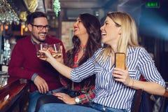 De vrienden kwamen na het werk in een bar voor een paar dranken bijeen - Beeld stock foto