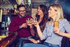 De vrienden kwamen na het werk in een bar voor een paar dranken bijeen - Beeld stock foto's
