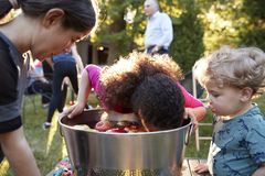 De vrienden letten de appel van het pre-tienermeisje op het bobbing bij binnenplaatspartij royalty-vrije stock afbeeldingen
