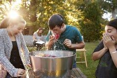 De vrienden letten tienerappel op het bobbing bij tuinpartij stock foto