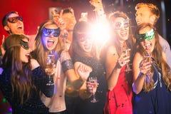 De vrienden in maskerade maskeert het drinken champagne stock afbeelding