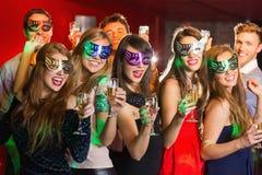 De vrienden in maskerade maskeert het drinken champagne royalty-vrije stock foto