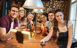 De vrienden met smartphone op selfie plakken bij bar Stock Afbeeldingen