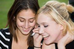 De vrienden op Cel telefoneren samen (Mooie Jonge Blonde en Brune Stock Afbeeldingen