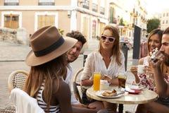 De vrienden op vakantie zitten het spreken buiten een koffie in Ibiza Royalty-vrije Stock Foto's