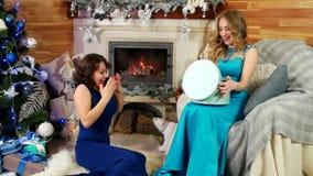 De vrienden ruilen Kerstmis voorstelt Nieuwjaar` s Vooravond, geeft het blije mooie wijfje een gift, zitten de meisjes door de op stock footage