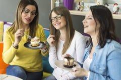 De vrienden spreken en eten cakes royalty-vrije stock afbeelding