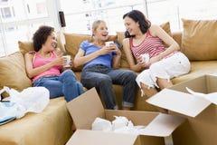 De vrienden van het meisje met koffie door dozen in nieuw huis Stock Foto