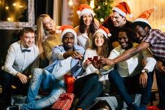 De vrienden van de Kerstmispartij bij het hebben van drank en pret stock afbeeldingen