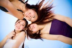 De vrienden verzamelen zich rond gelukkig onder heldere blauwe hemel Stock Foto's