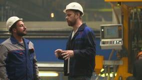 De vriendeningenieurs komen in de industrieinstallatie samen en bespreken plannen stock video