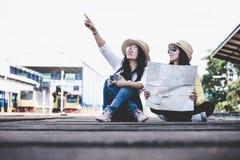 De vriendenvrouwen die van de toeristen Aziatische levensstijl de kaart van de rugzakholding, reiziger dragen die voor het wachte royalty-vrije stock foto
