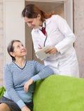 De vriendschappelijke arts vraagt de blije patiënt voelt Stock Foto