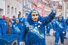 De vriendschappelijke Carnaval-heks in blauwe rode robe, bekijkt diagonaal de camera In Carnaval in zuidelijk Duitsland royalty-vrije stock afbeeldingen