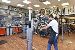 De vriendschappelijke en bekwame fietswerktuigkundige in een workshop herstelt een fiets royalty-vrije stock fotografie