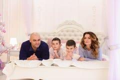 De vriendschappelijke familie babbelt het liggen op bed, mamma en papa met hun kind Stock Foto's