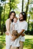 De vriendschappelijke familie gekleed in de witte kleren neemt rust in het park De papa en het mamma koesteren hun kinderen royalty-vrije stock fotografie