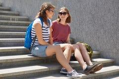 De vriendschappelijke klasgenoten genieten van vrije tijd, stellen op stappen in het stedelijke plaatsen, gekleed in t-shirts en  stock afbeelding