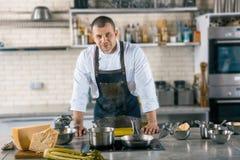 De vriendschappelijke kok situeert in luchtige keuken kok die ravioli voorbereidingen treffen te koken stock afbeeldingen
