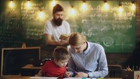 De vriendschappelijke leraren en de kindjongen trekken in klaslokaal De leraar creeert betekenis van communautair en het behoren  stock footage