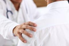 De vriendschappelijke mannelijke geduldige schouder van de artsengreep in bureau tijdens rece Stock Fotografie