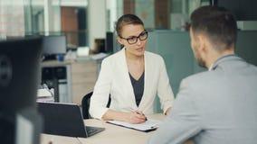 De vriendschappelijke onderneemster in glazen en kostuum interviewt een mannelijke kandidaat voor baan in bureau De mensen spreke stock footage
