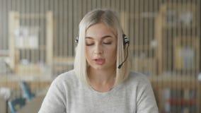 De vriendschappelijke persoon van de meisjestechnische ondersteuning of call centremanager in het bureau stock videobeelden