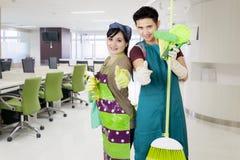 De vriendschappelijke schoonmakende dienst klaar om vergaderzaal schoon te maken royalty-vrije stock foto's