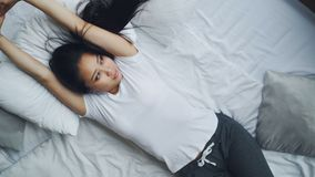 De vrij Aziatische dame slaapt op bed die dan ogen openen en haar wapens met glimlach uitrekken Zacht hoofdkussen en wit linnen stock videobeelden
