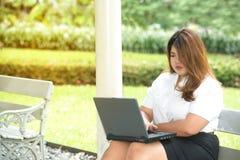 De vrij Aziatische vette vrouw stelt het werken met laptop aan een stoel Stock Foto's
