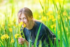 De vrij blonde vrouw ruikt gele bloemen Stock Foto's