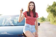 De vrij donkerbruine jonge Europese vrouw toont autosleutel, verheugt zich nieuwe aankoop, stelt dichtbij nieuwe auto, gekleed in royalty-vrije stock foto's