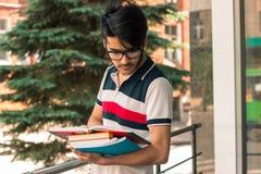 De vrij donkerbruine student met boeken in handen draagt glazen Royalty-vrije Stock Afbeeldingen